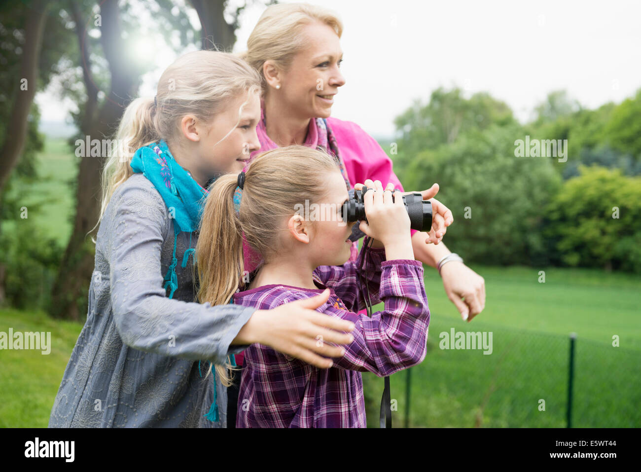 Mother and daughters using binoculars - Stock Image