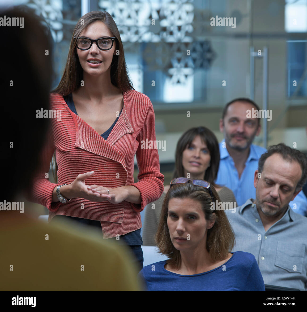 Woman standing in middle of group - Stock Image