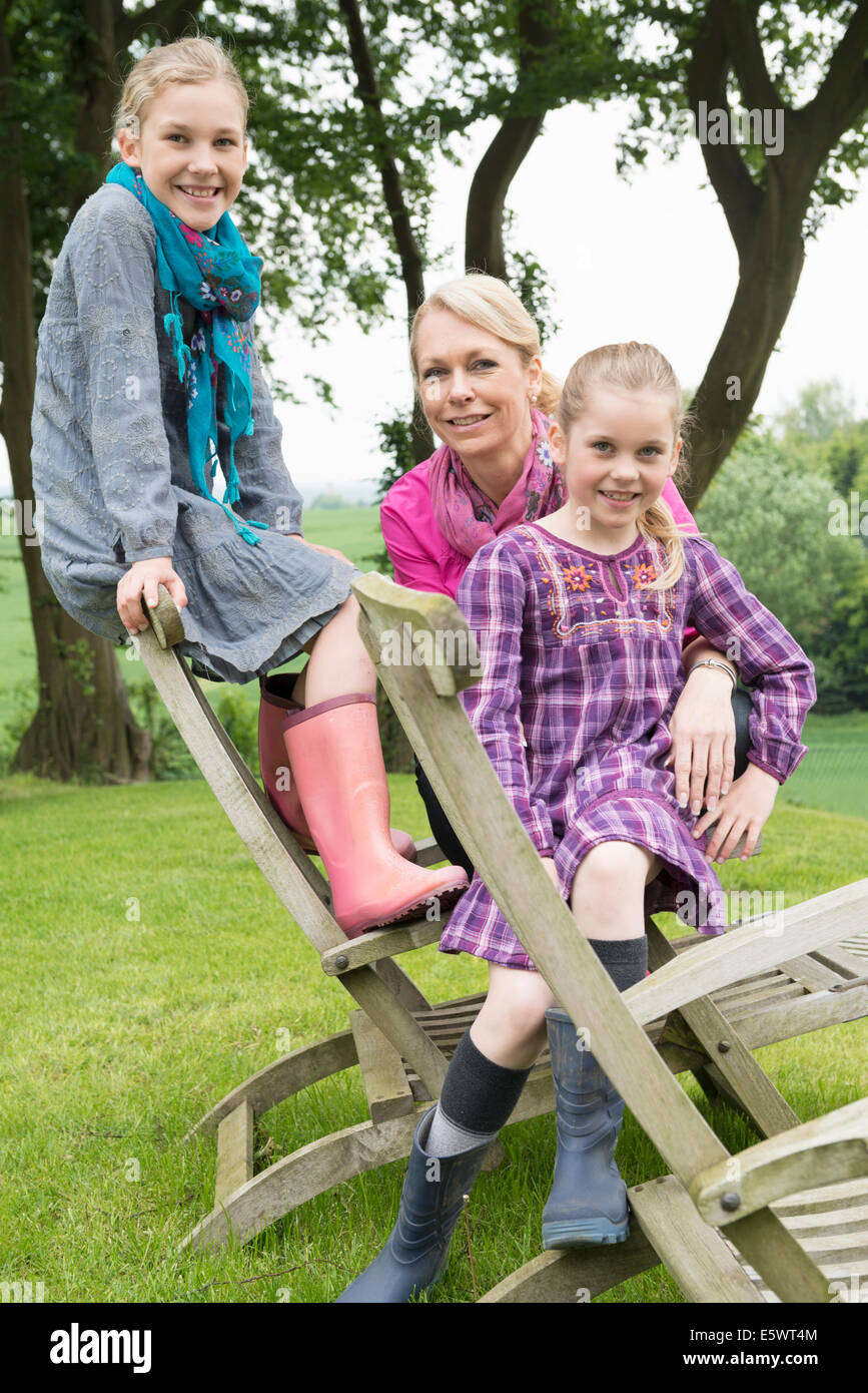 Mother and daughters sitting on wooden chair, portrait - Stock Image