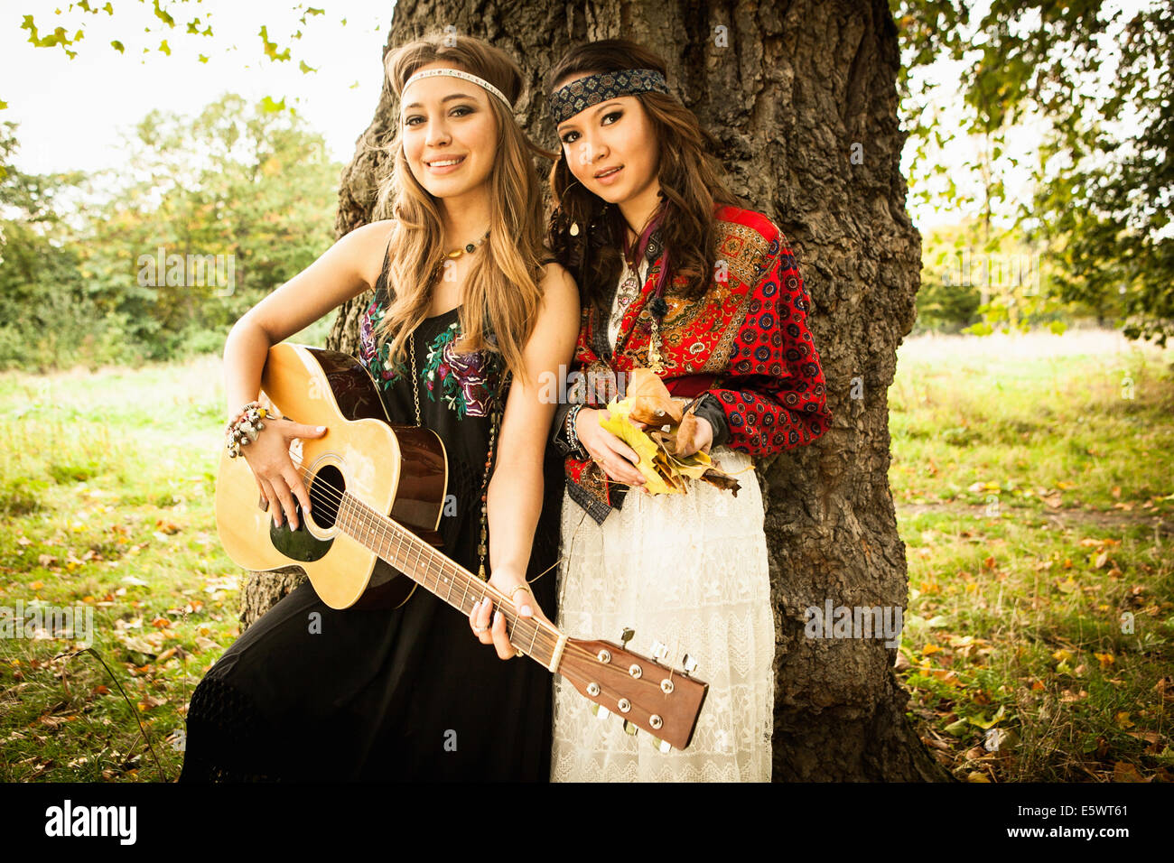Hippy girls by tree with guitar - Stock Image