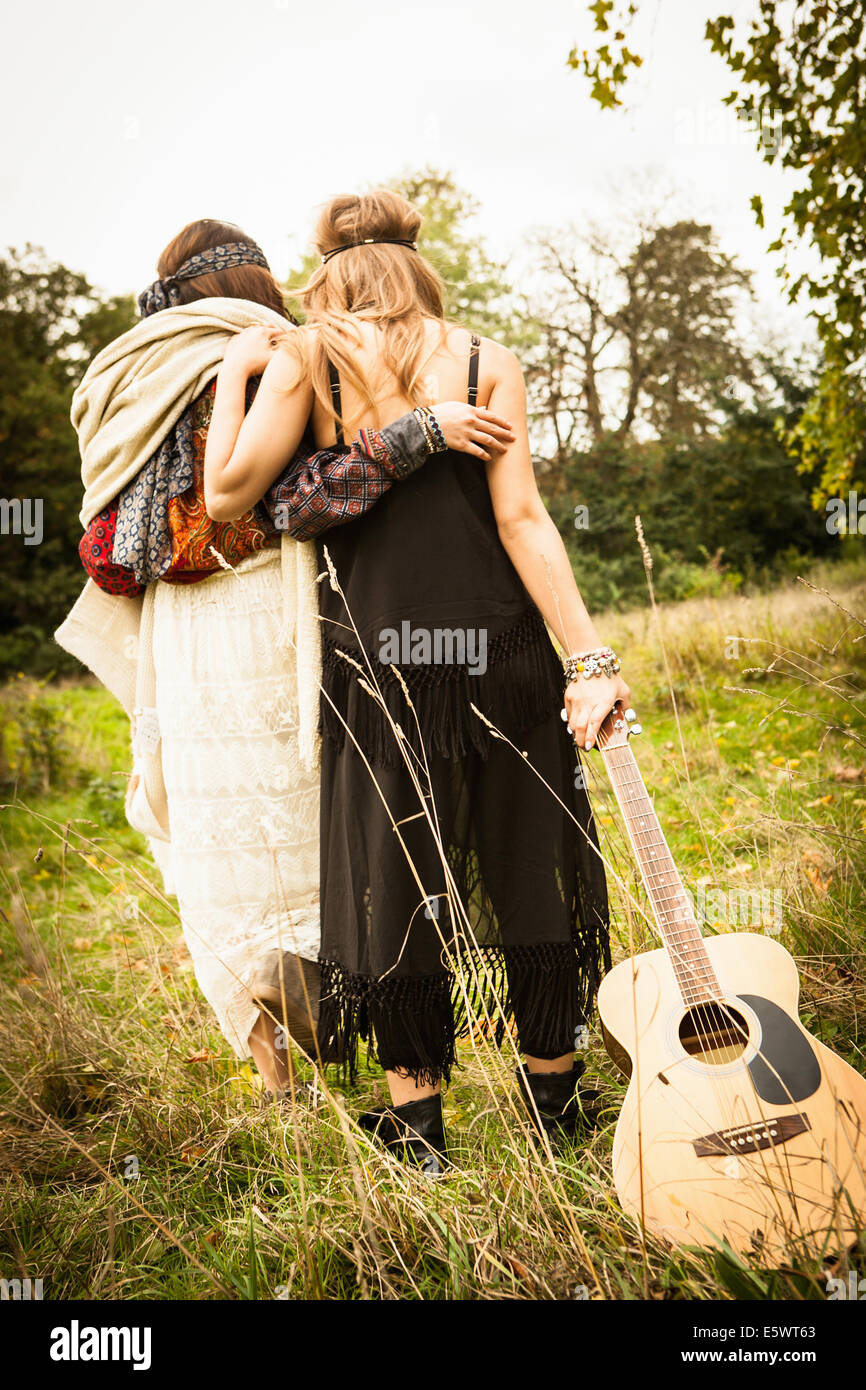 Rear view of hippy girls walking through field with guitar - Stock Image