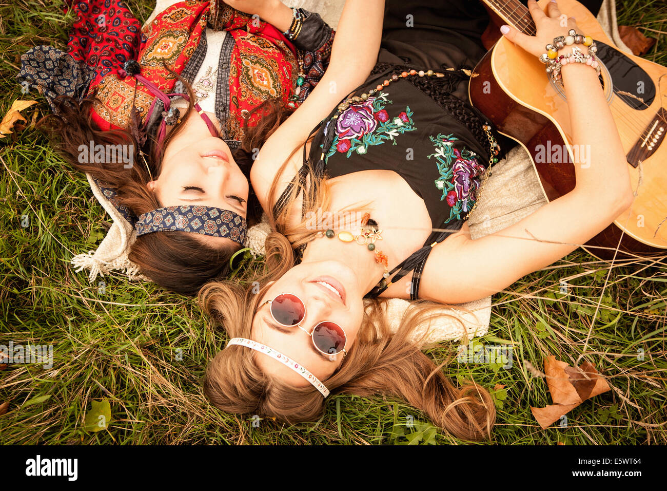Hippy girls lying in field with guitar - Stock Image