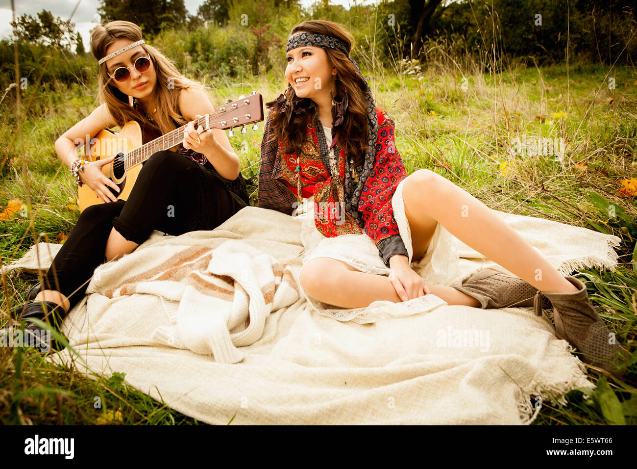 Hippy girls on blanket in field, playing guitar - Stock Image