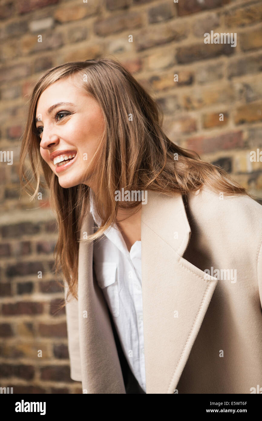Woman with wide smile, brick wall in background - Stock Image