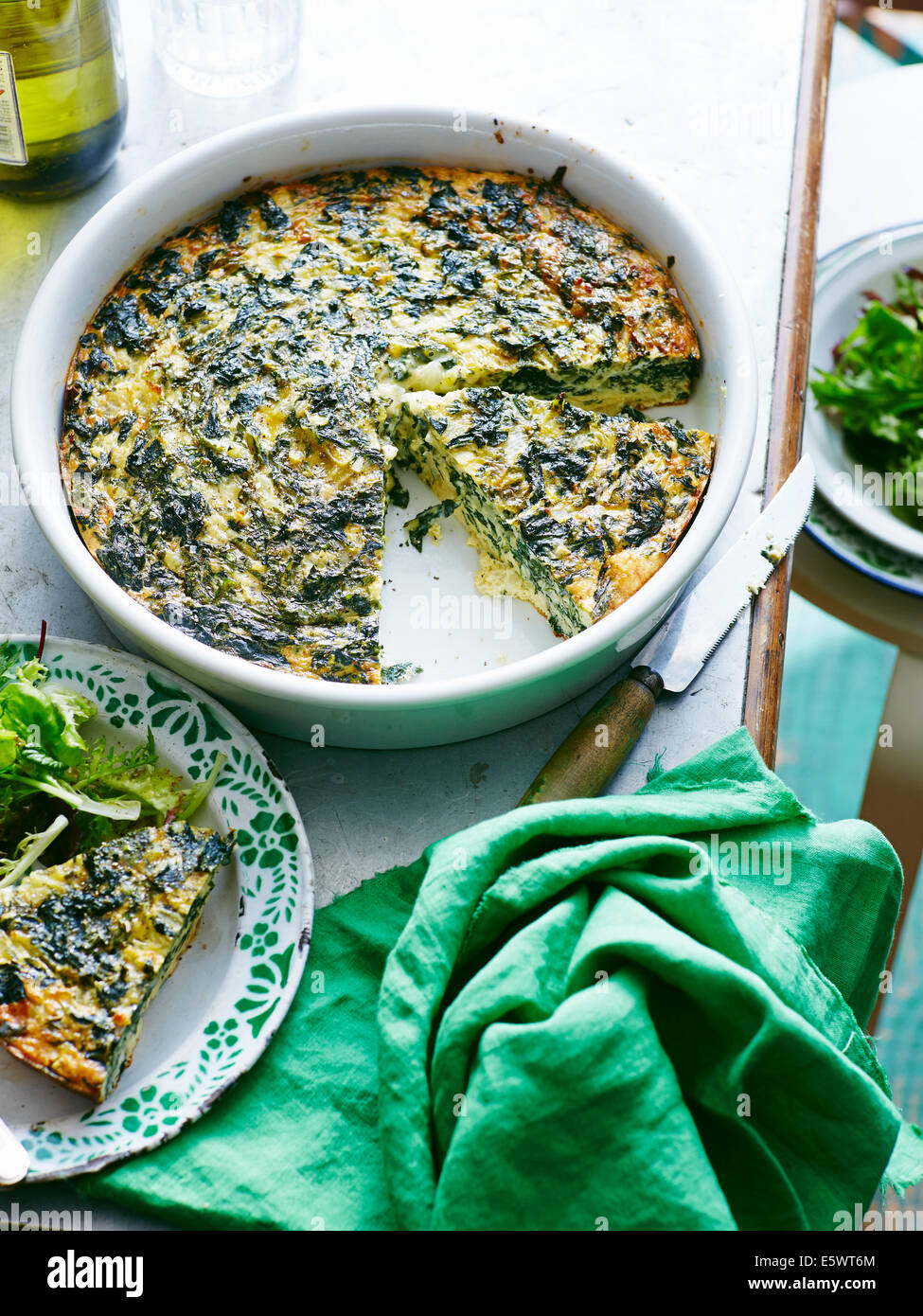 Dish of silverbeet and feta frittata with portion on plate - Stock Image