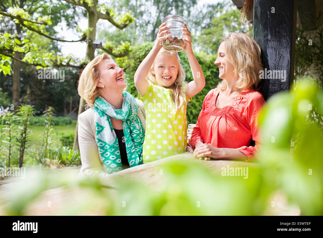 Girl opening jar of coins with family Stock Photo