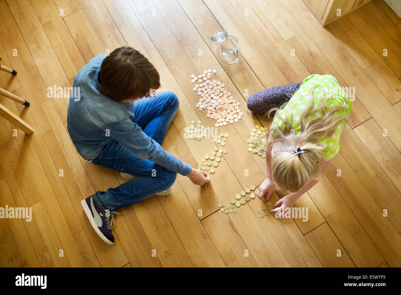 Brother and sister counting coins from savings jar - Stock Image