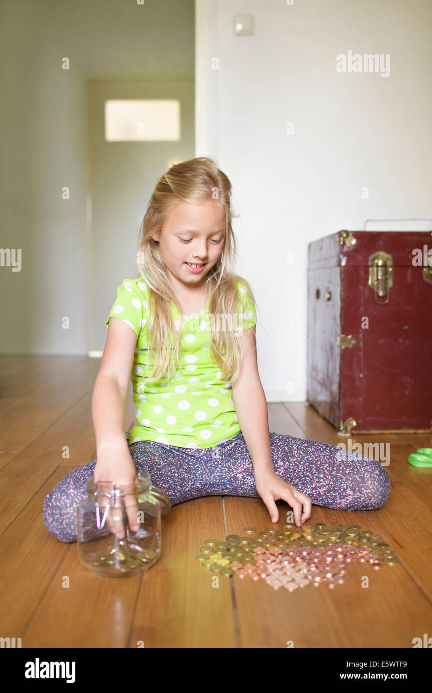 Girl counting coins from savings jar - Stock Image