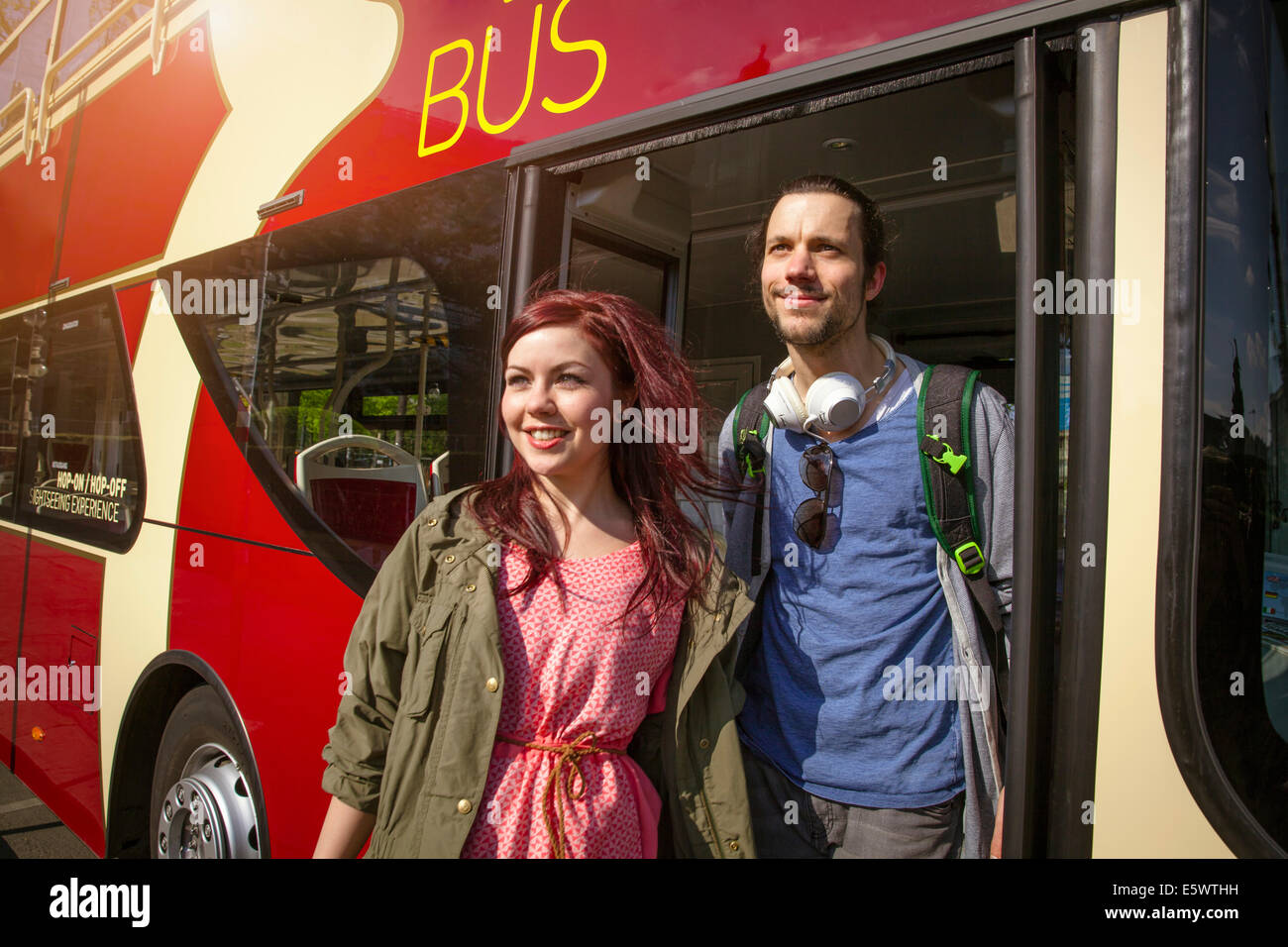 Young adult couple getting off bus - Stock Image