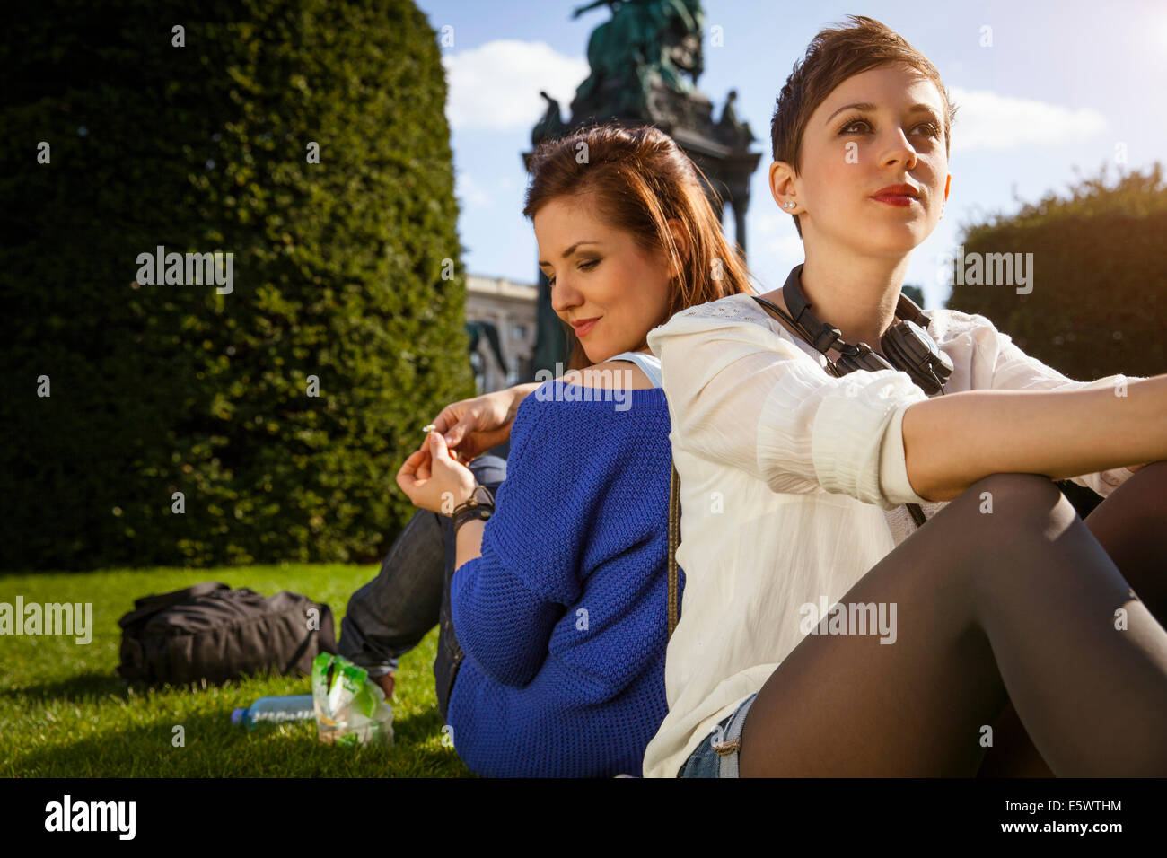 Two young adult women sitting back to back in park - Stock Image