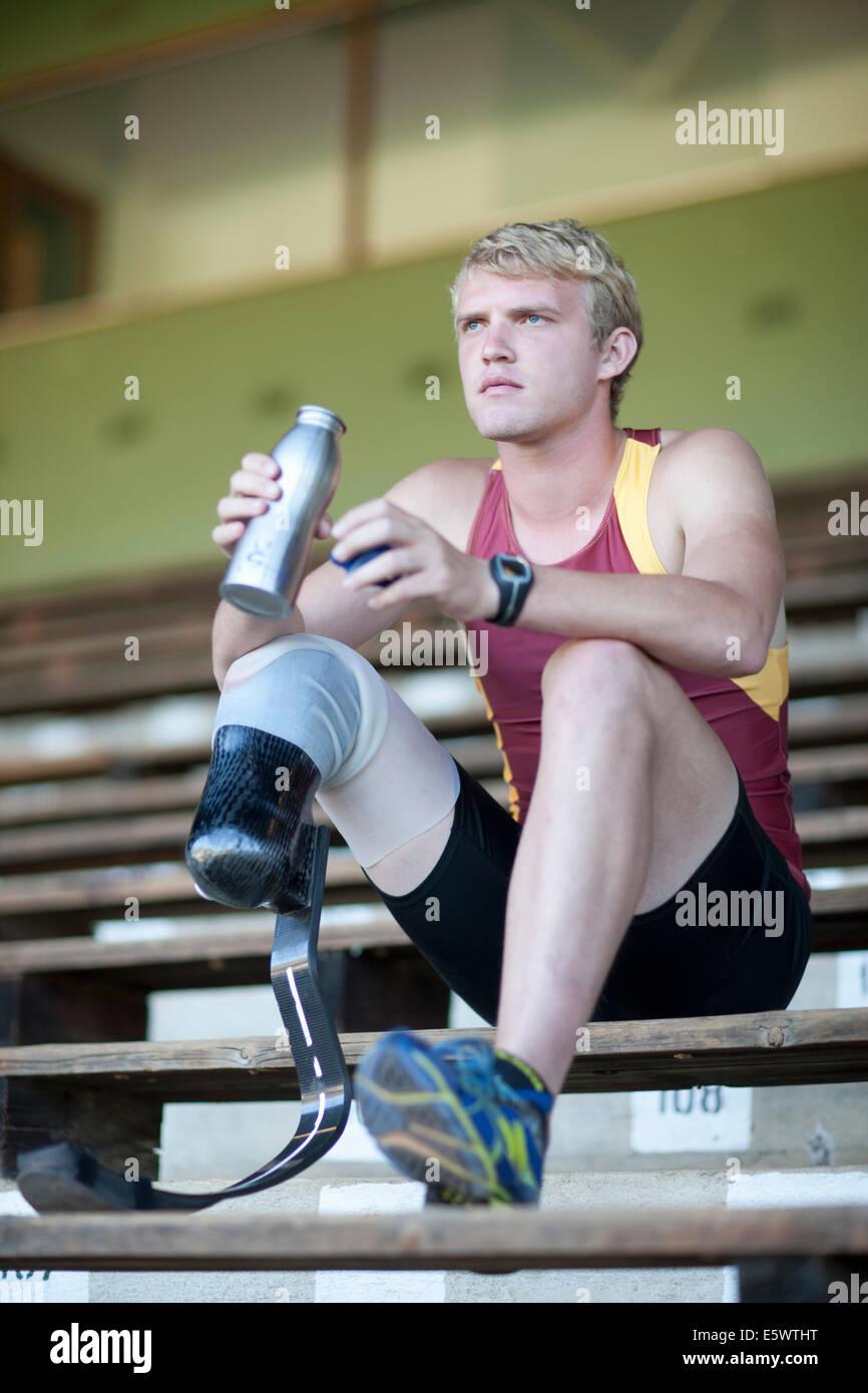 Sprinter sitting with prosthetic leg on - Stock Image