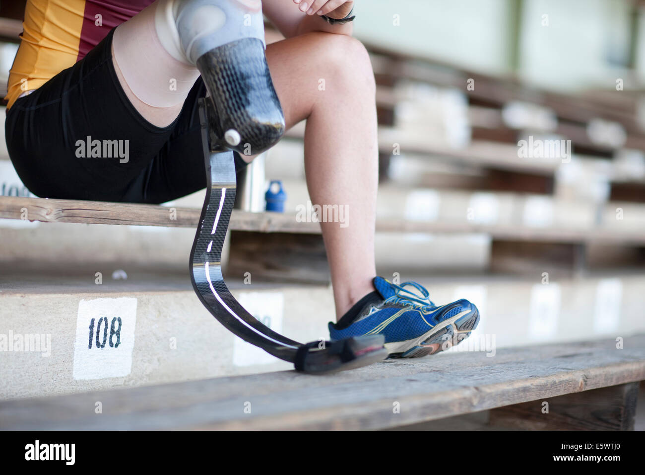 Sprinter sitting with prosthetic leg on - Stock Image
