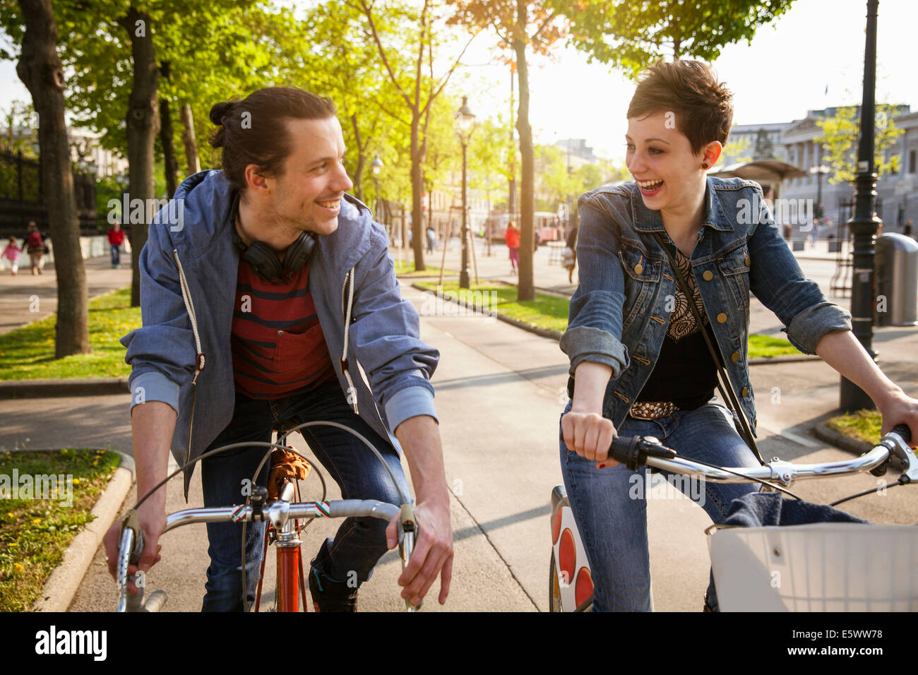 Young adult couple cycling through city, Vienna, Austria - Stock Image