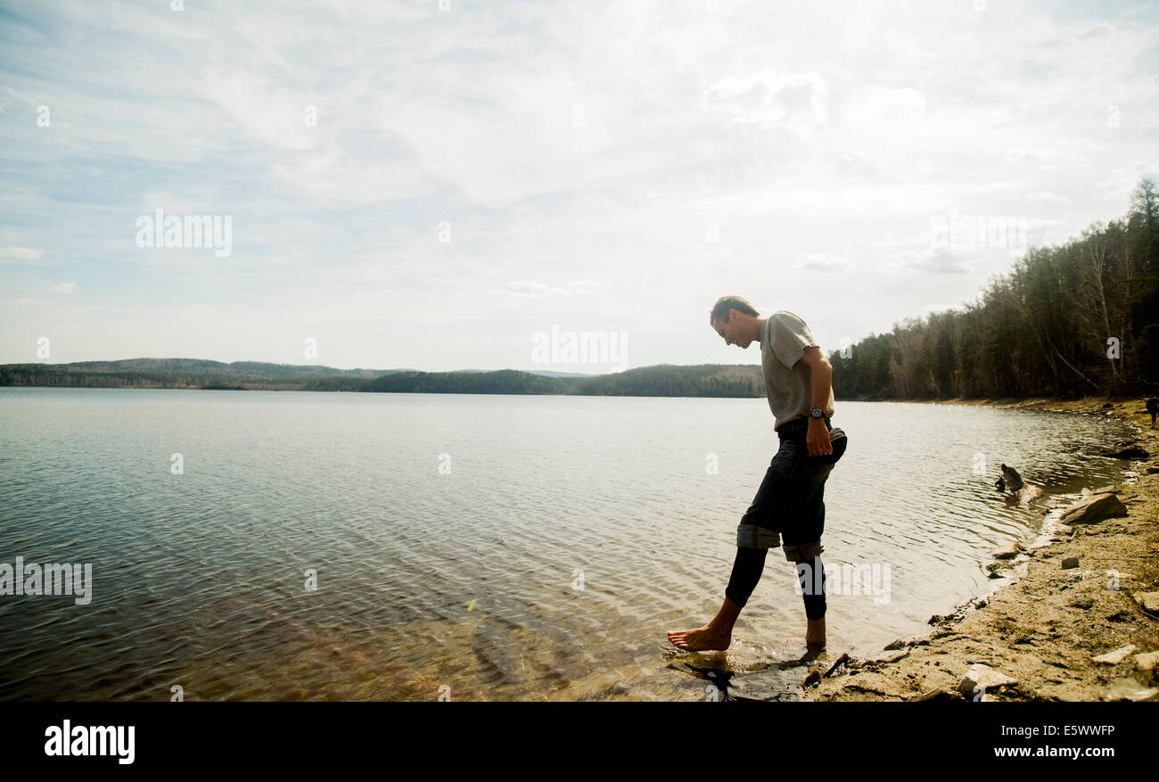 Young male hiker taking apprehensive paddle in lake - Stock Image