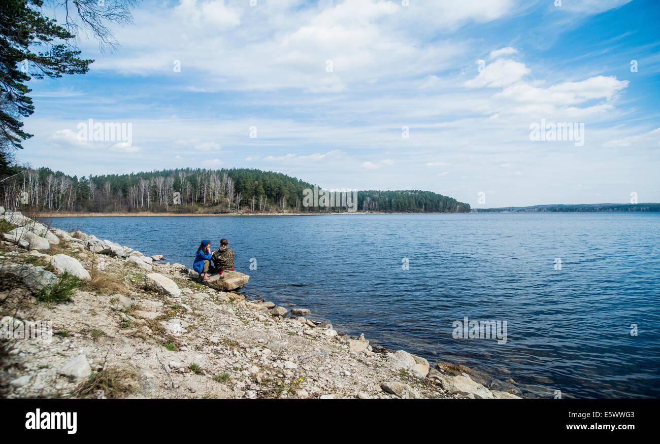 Two female hiking friends taking a break on lakeside - Stock Image