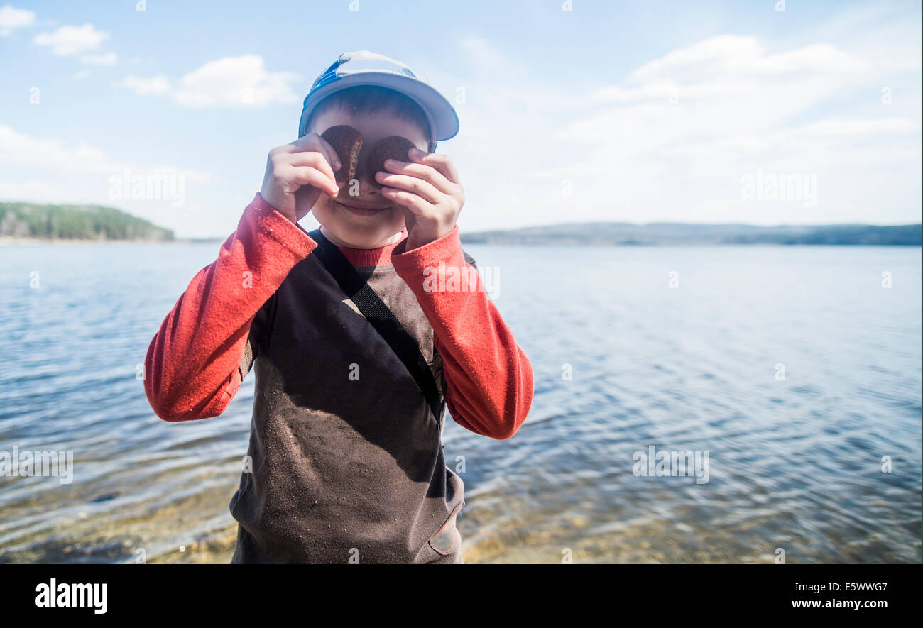 Portrait of mischievous boy with biscuits over eyes at lakeside - Stock Image