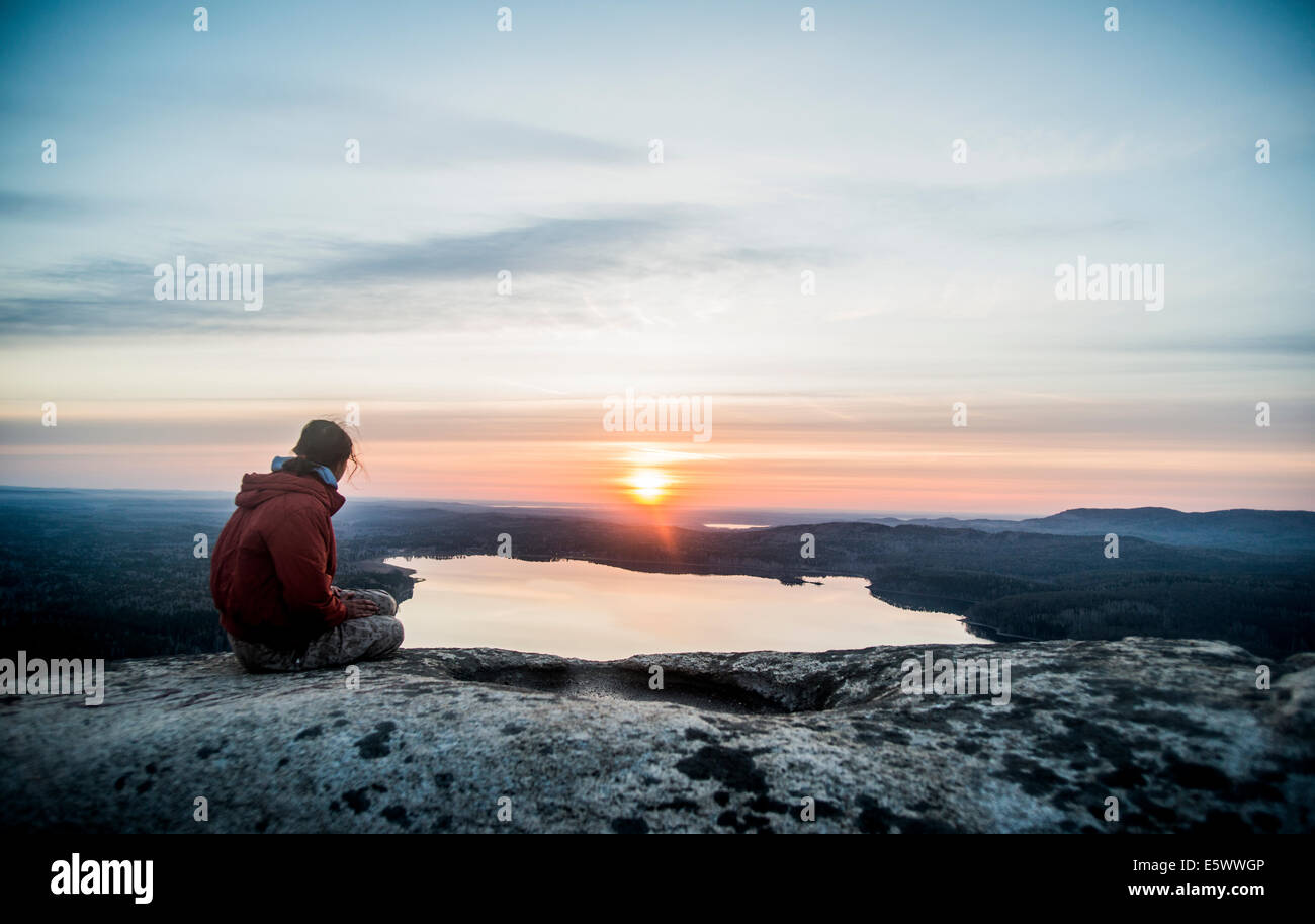 Young female hiker gazing at sunset over distant lake - Stock Image