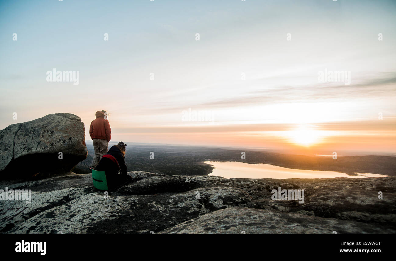 Two young female hikers gazing at sunset over distant lake - Stock Image