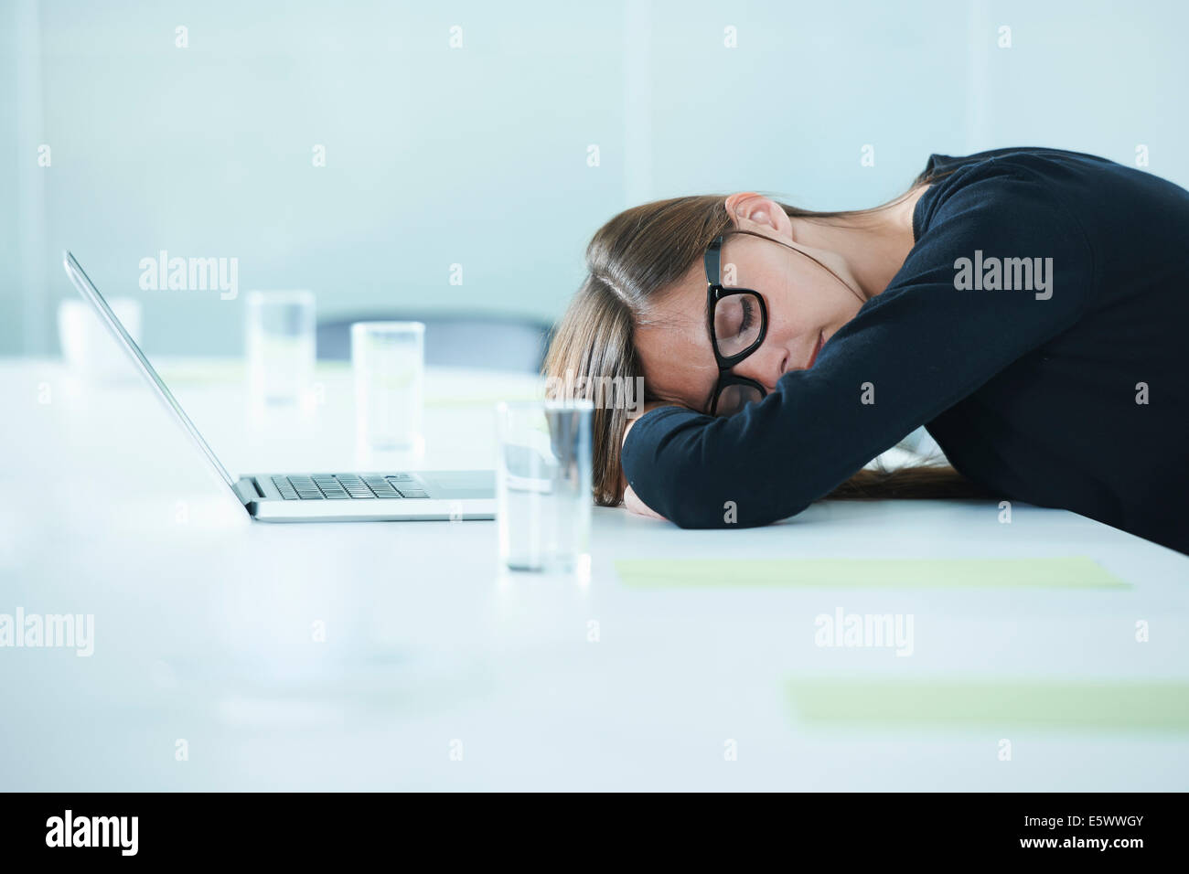 Female office worker asleep at conference table - Stock Image