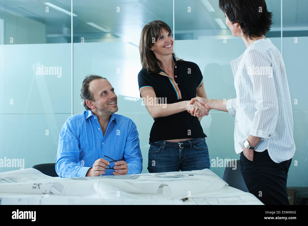 Architect greeting client with blueprints on boardroom table - Stock Image