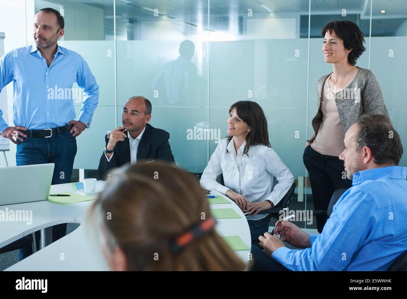 Informal business meeting around boardroom table - Stock Image
