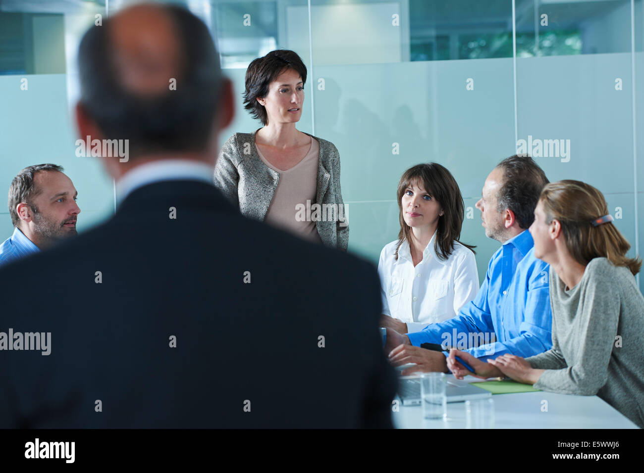 Businessmen and women arguing around boardroom table - Stock Image