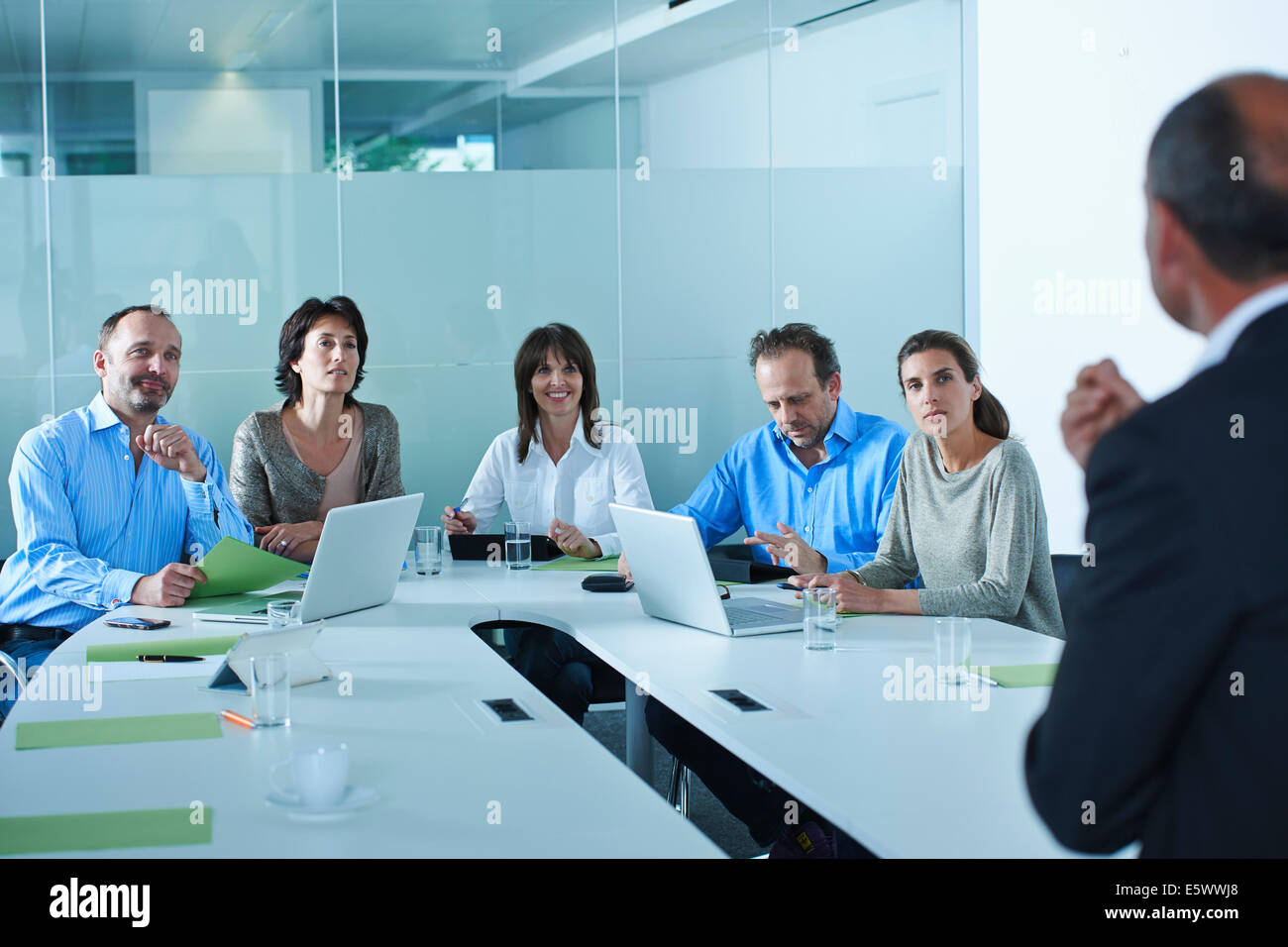 Business team interviewing candidate at boardroom table - Stock Image