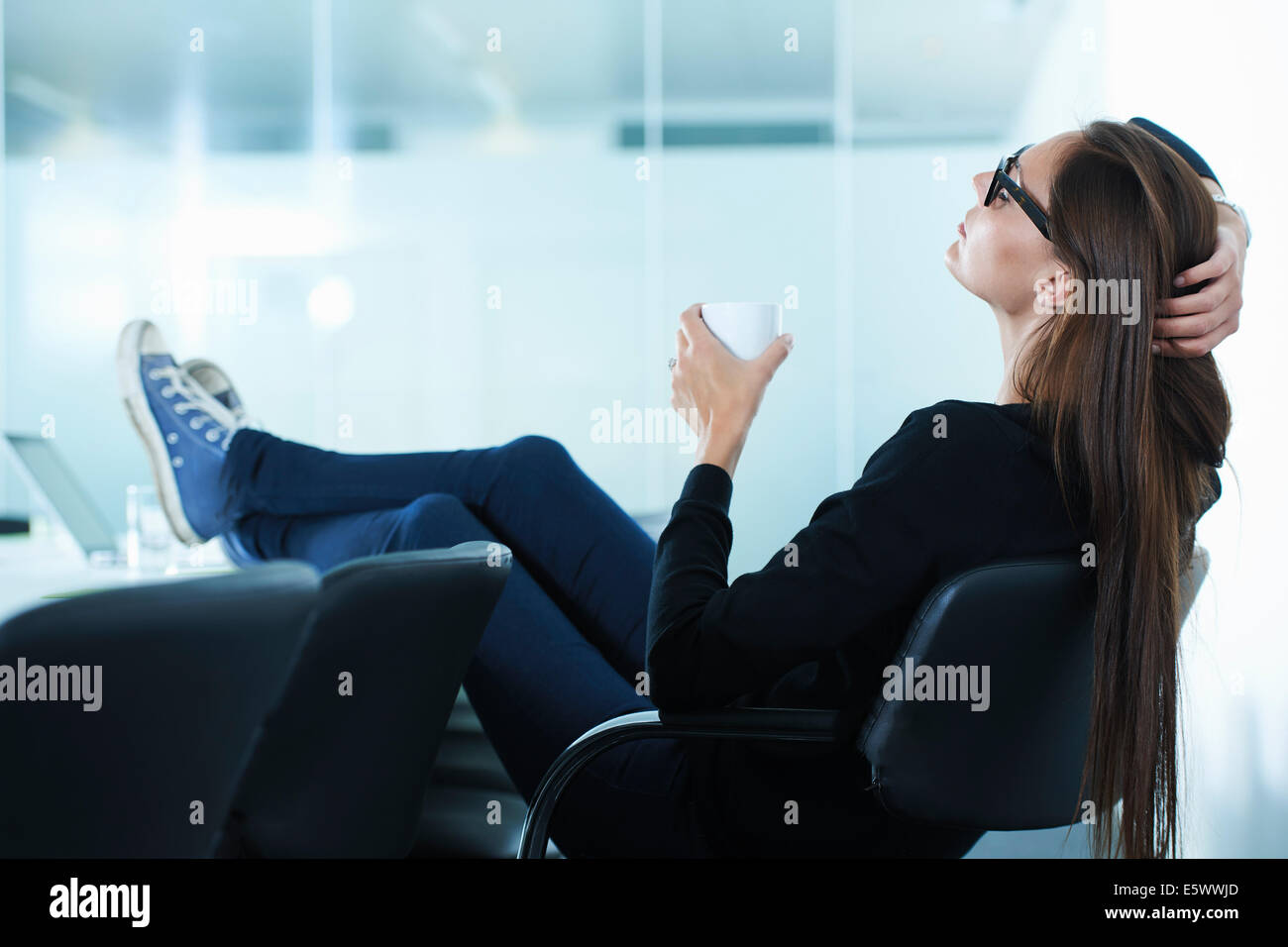 Female office worker leaning back with feet up on conference table Stock Photo