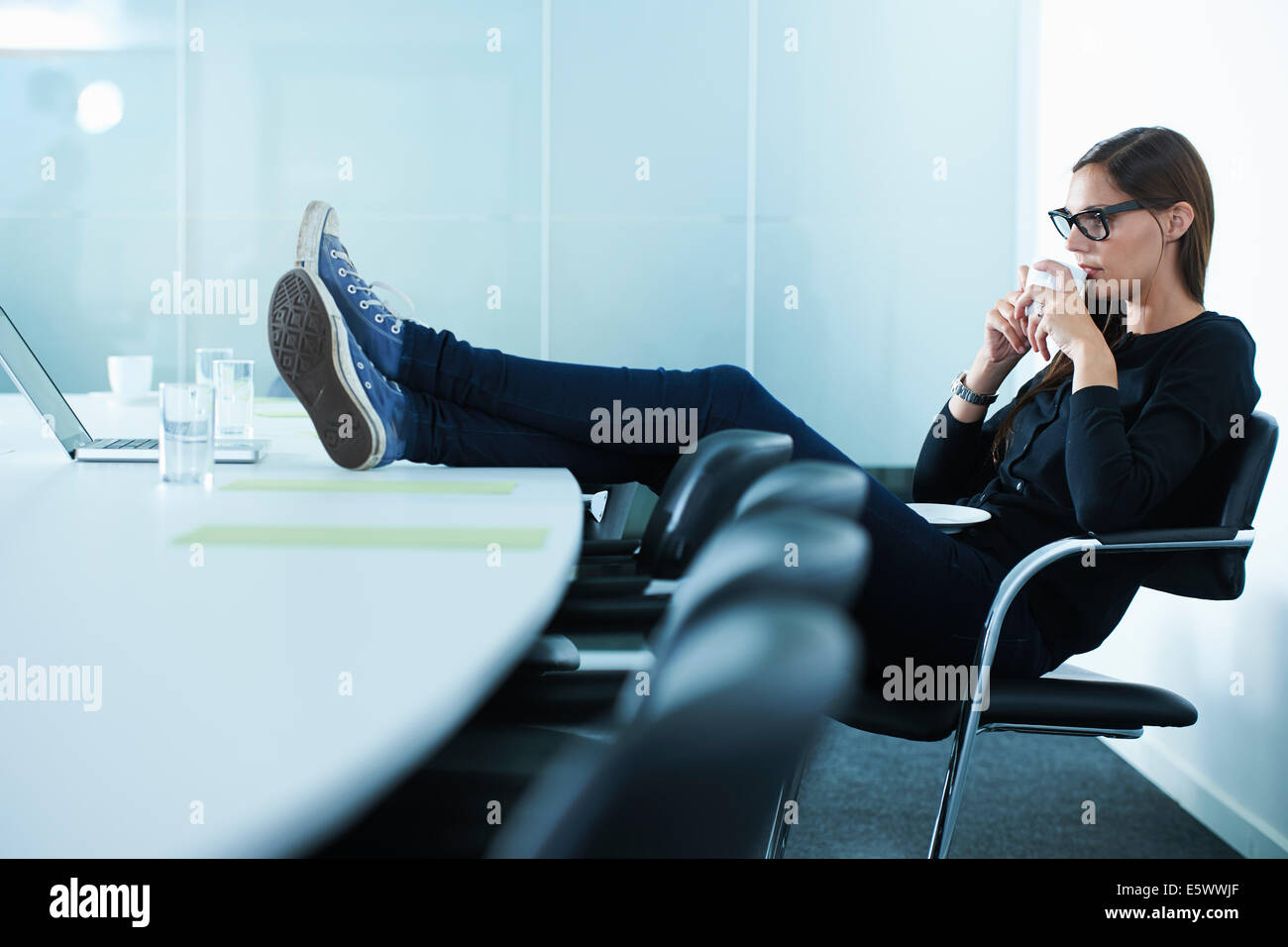 Female office worker drinking coffee with feet up on conference table Stock Photo