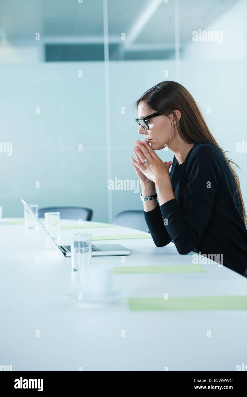 Worried female office worker using laptop at conference table - Stock Image