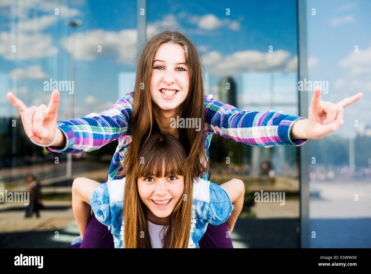 Two young women piggybacking making I love you hand gesture - Stock Image