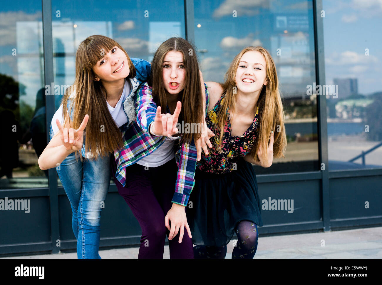 Three young women leaning forward in a row and making I love you hand gesture - Stock Image