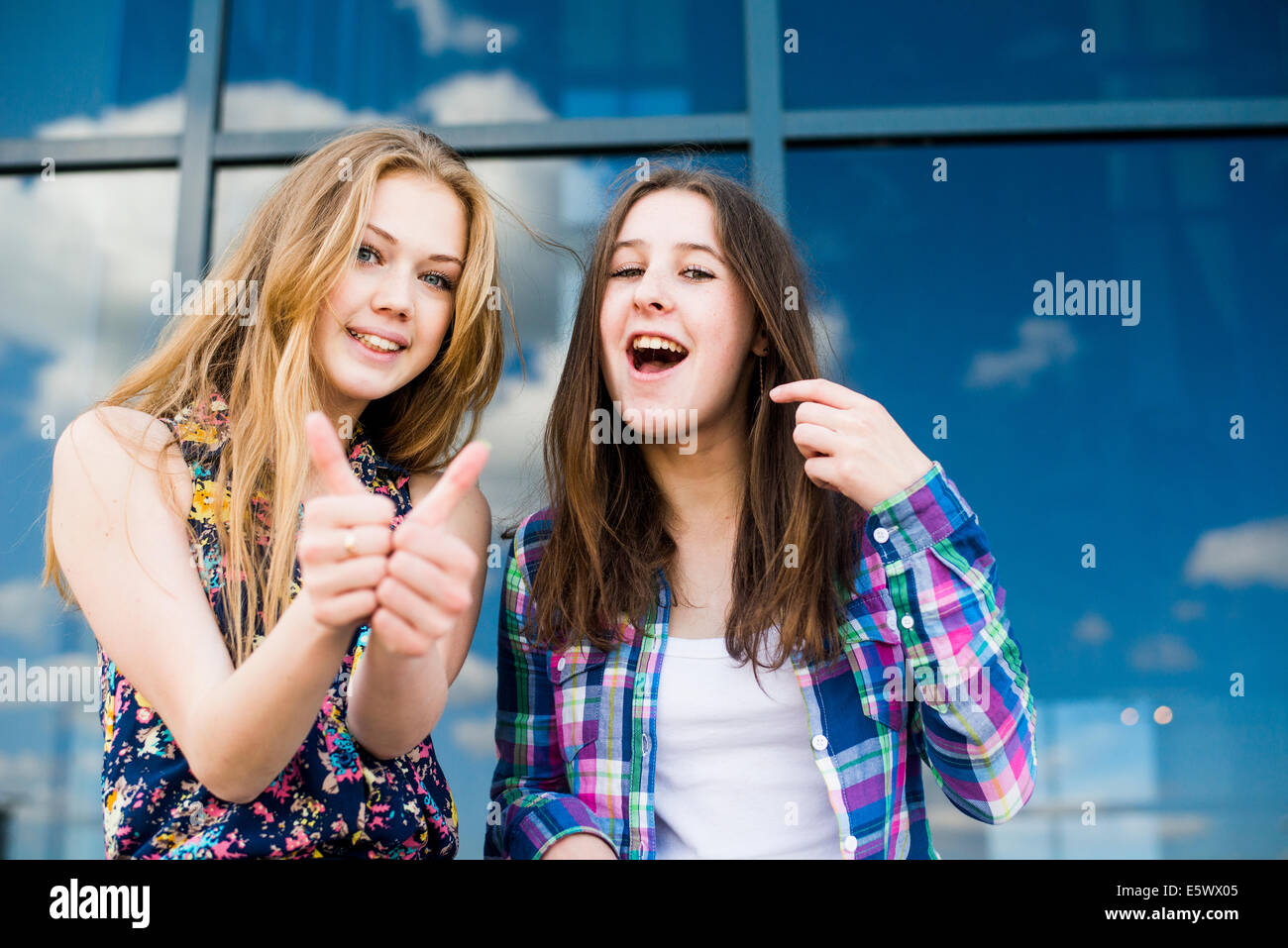 Portrait of two young women making thumbs up in front of glass fronted office - Stock Image