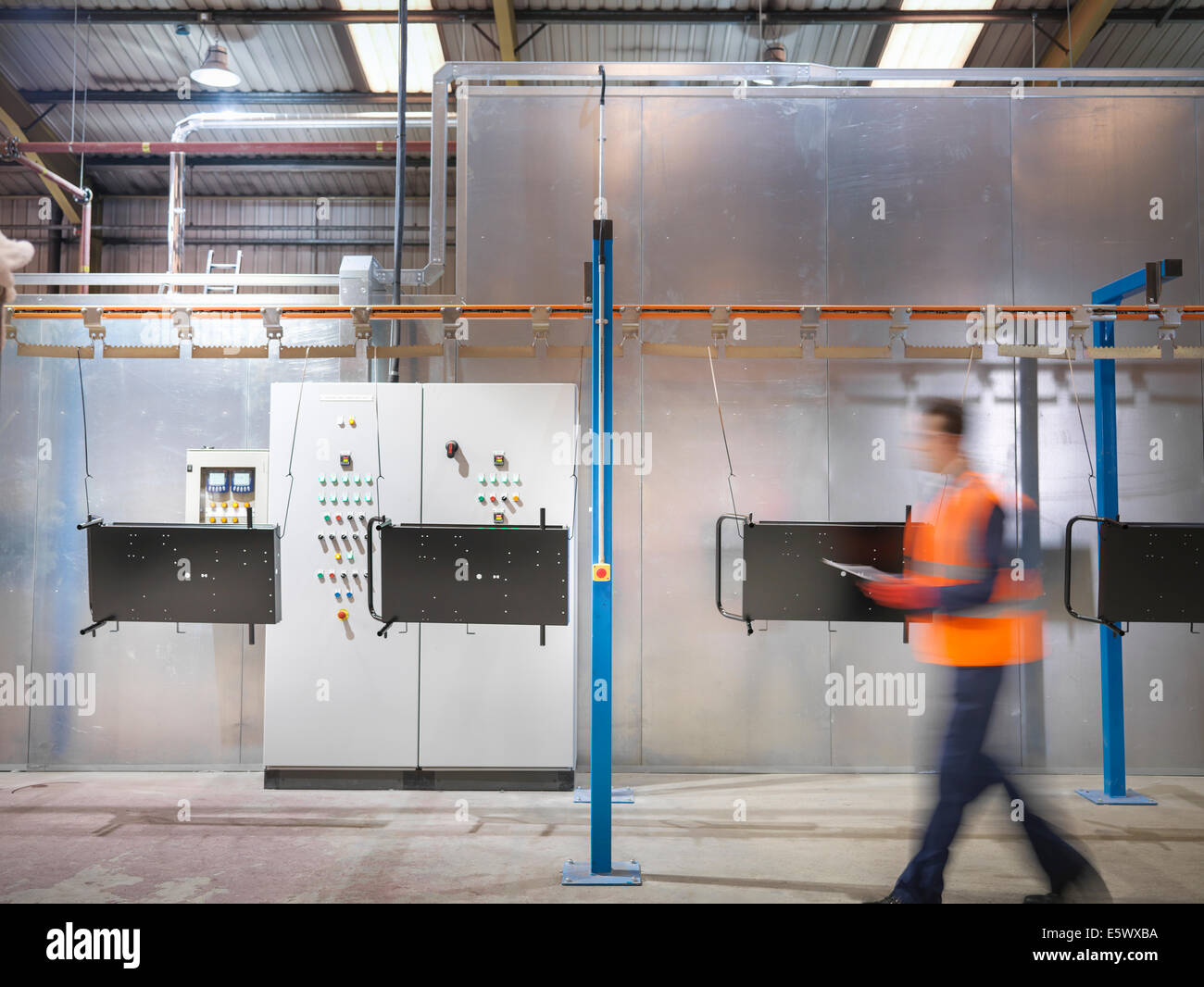Worker with clipboard walking past paint spray machine in sheet metal factory - Stock Image