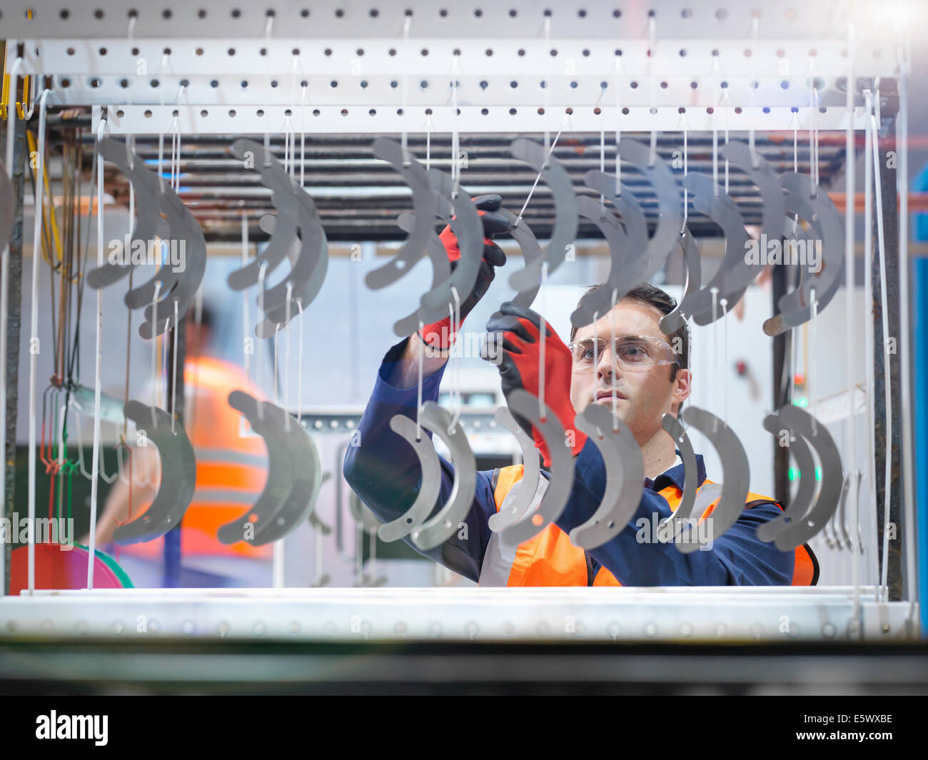 Worker arranging metal parts for paint spraying in sheet metal factory - Stock Image
