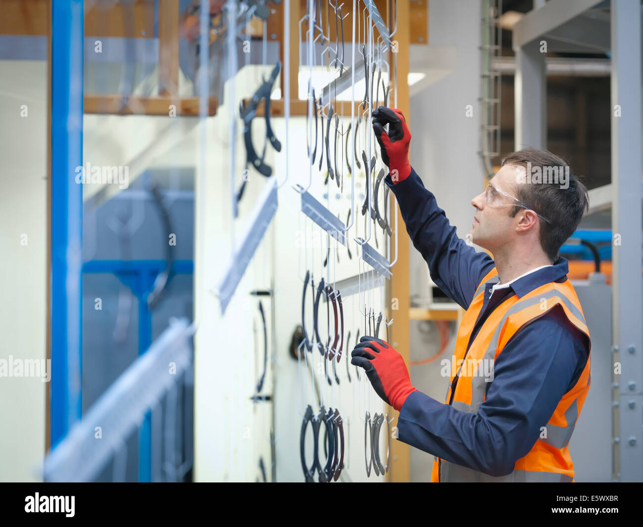 Worker inspecting painted parts in sheet metal factory - Stock Image