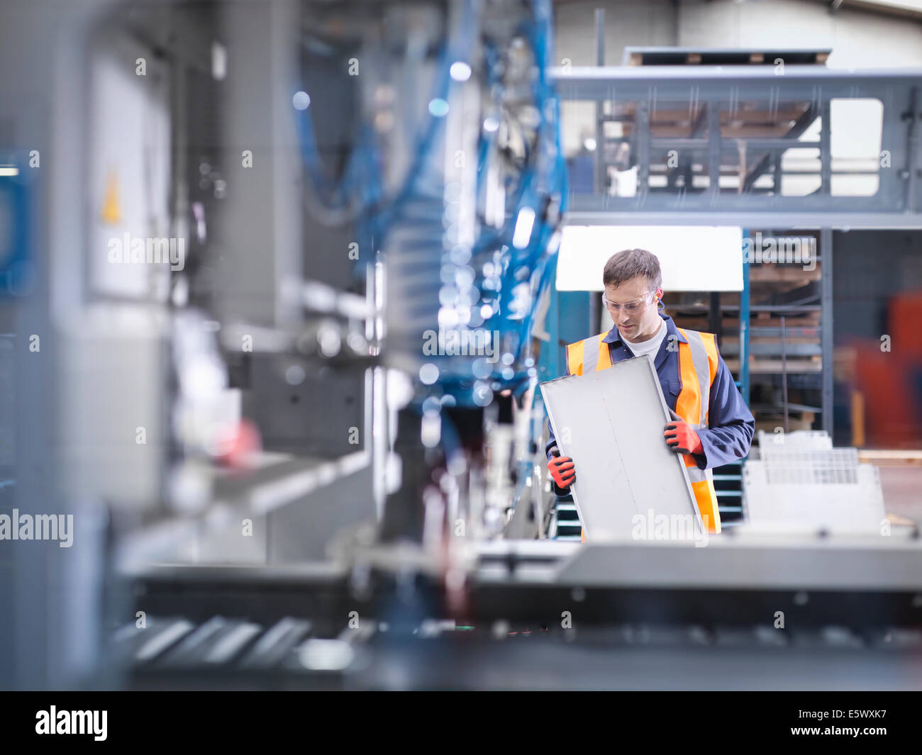 Worker inspecting parts next to robotic metal cutting machine in sheet metal factory - Stock Image
