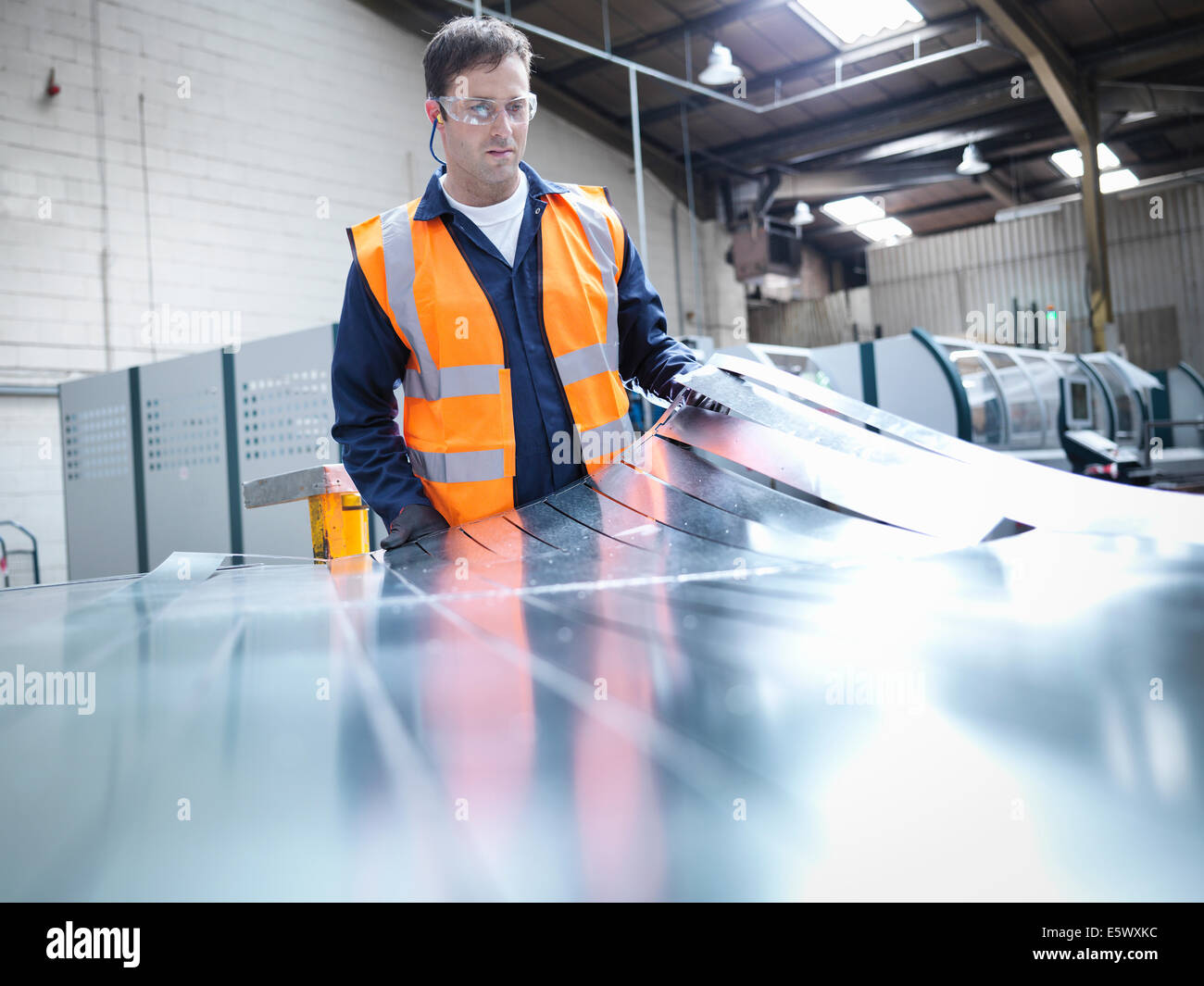 Worker inspecting newly cut parts in sheet metal factory - Stock Image