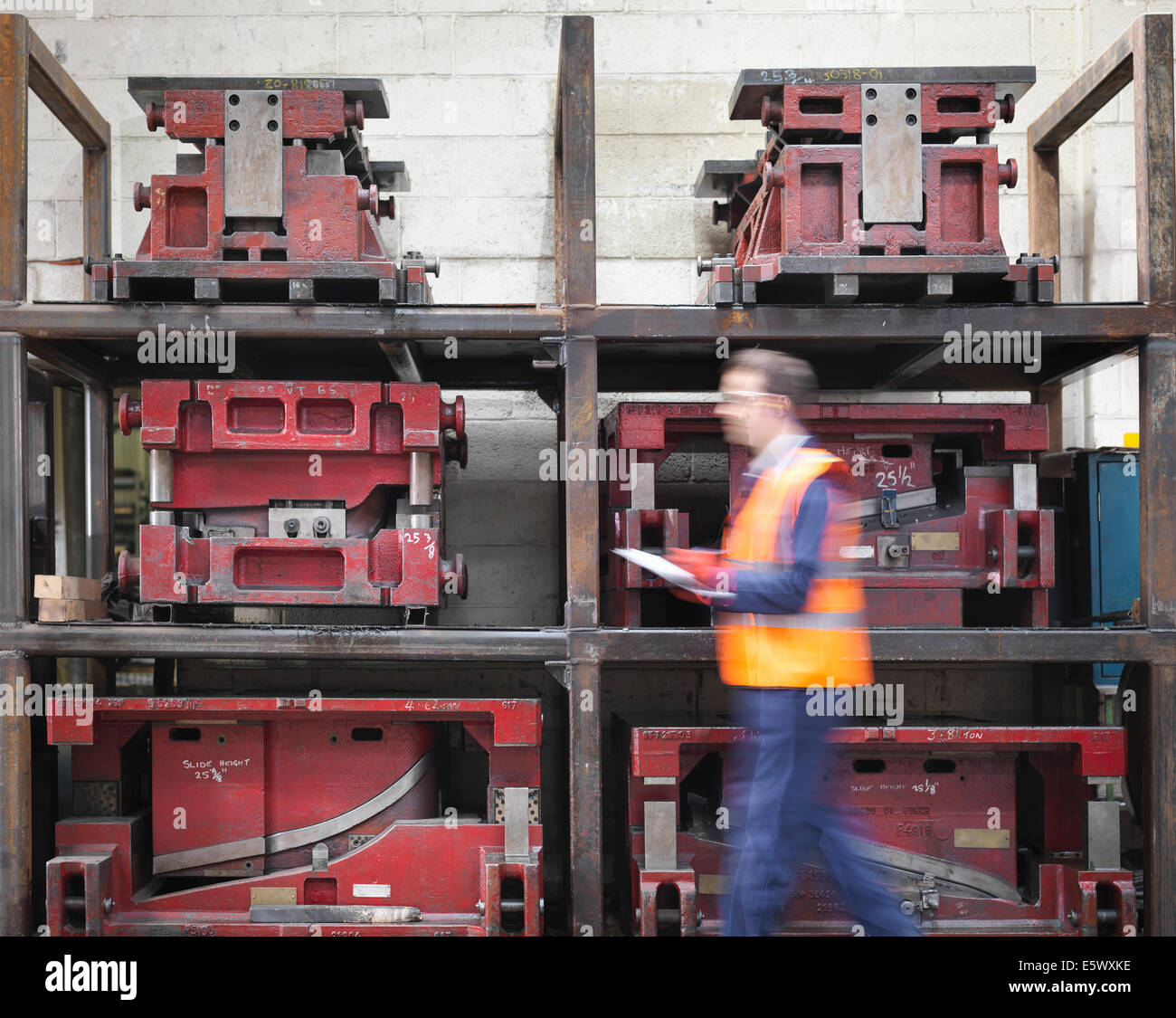 Worker with clipboard walking past press moulds in sheet metal factory - Stock Image