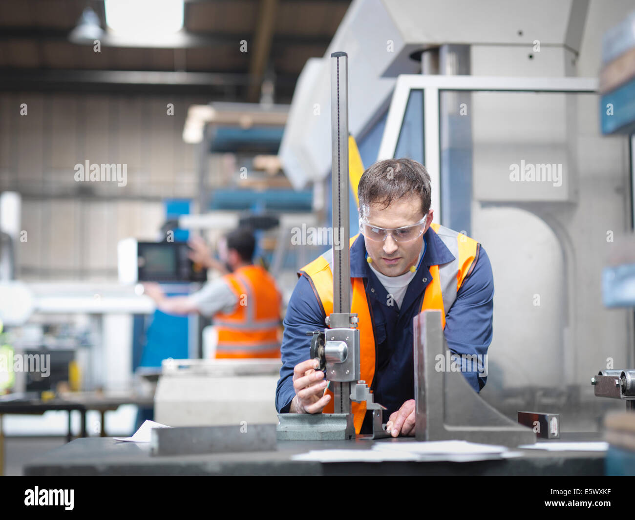 Worker measuring parts in sheet metal factory - Stock Image