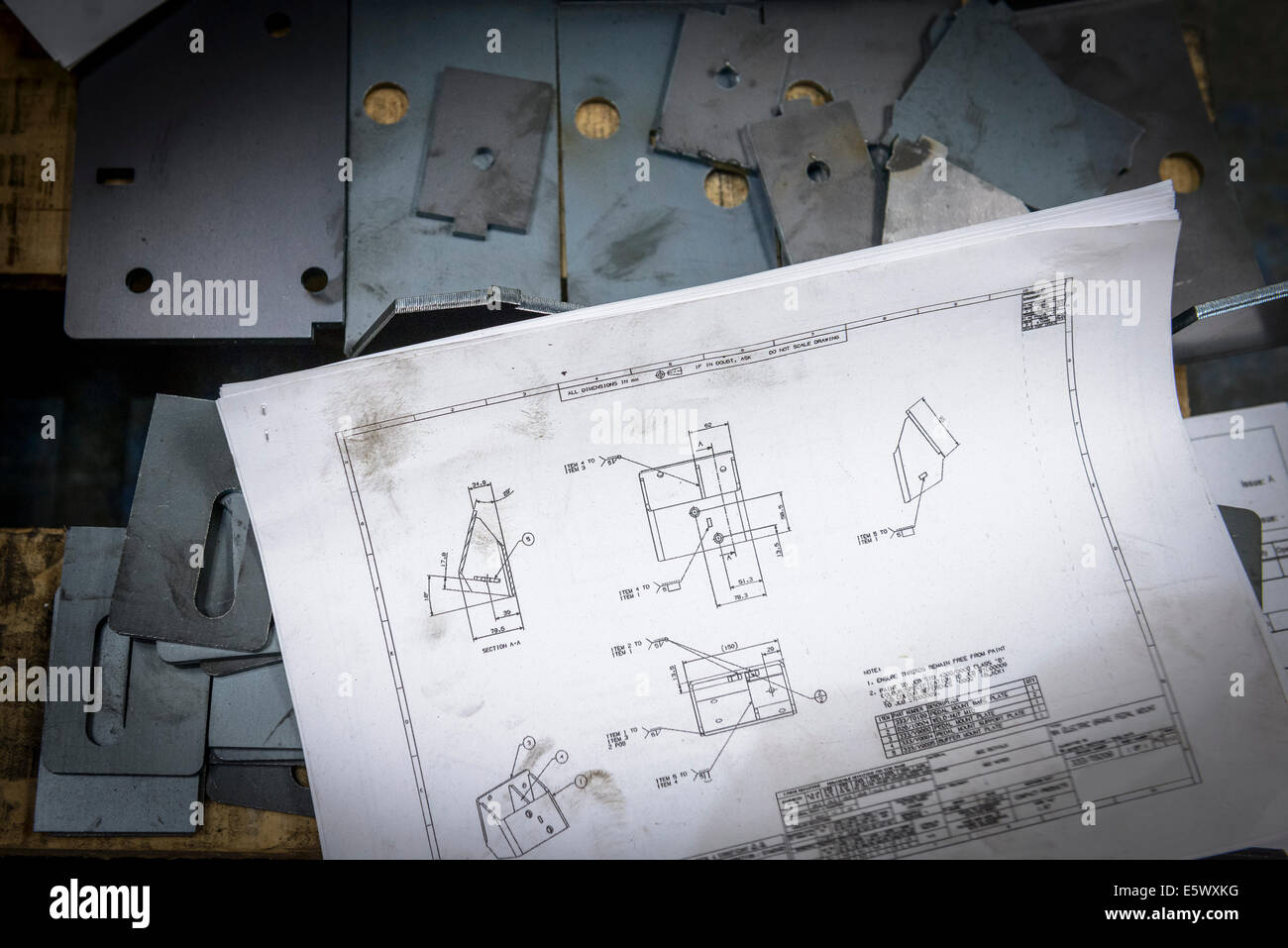 Engineering drawings and parts in sheet metal factory - Stock Image