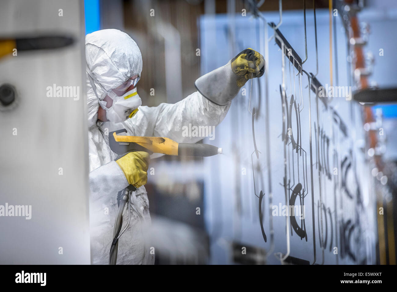 Worker powder coating parts in paint spray booth in sheet metal factory - Stock Image