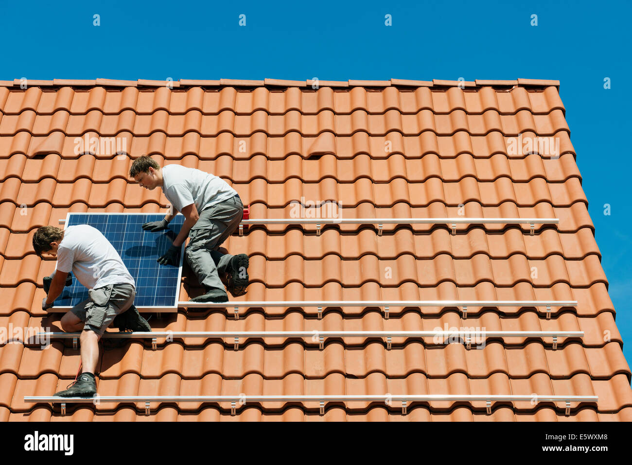 Workers installing solar panel on roof framework of new home, Netherlands - Stock Image