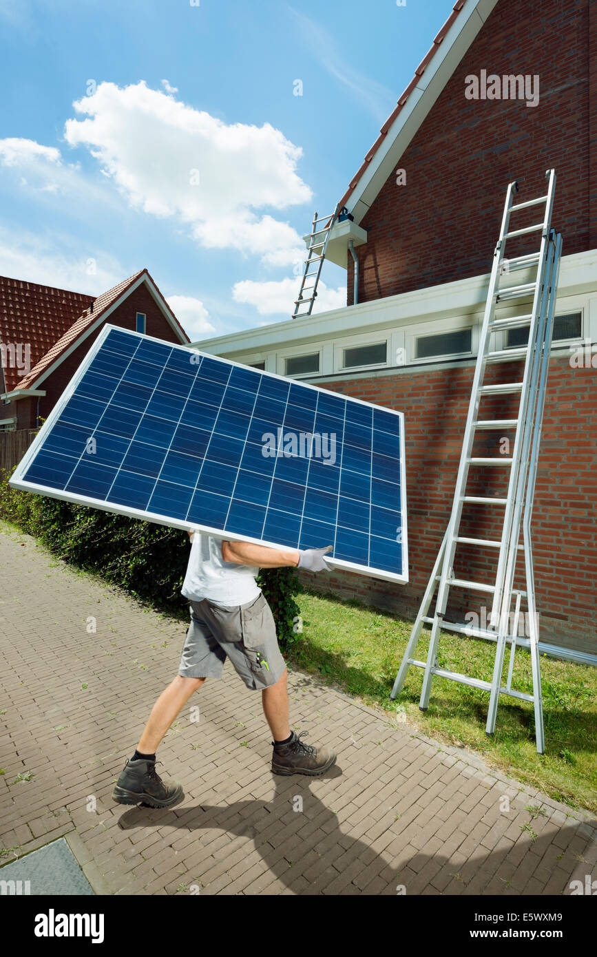 Worker carrying solar panel for roof of new home, Netherlands - Stock Image