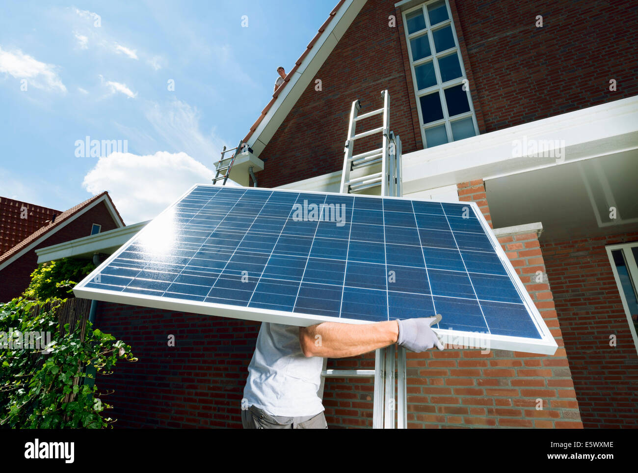 Worker Climbing Ladder Carrying Solar Panel For Roof Of