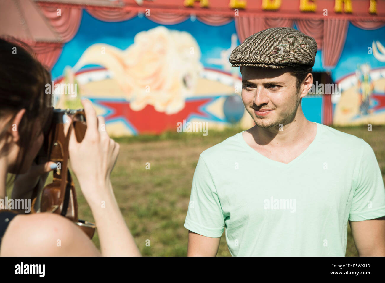 Young couple photographing on SLR camera at funfair - Stock Image