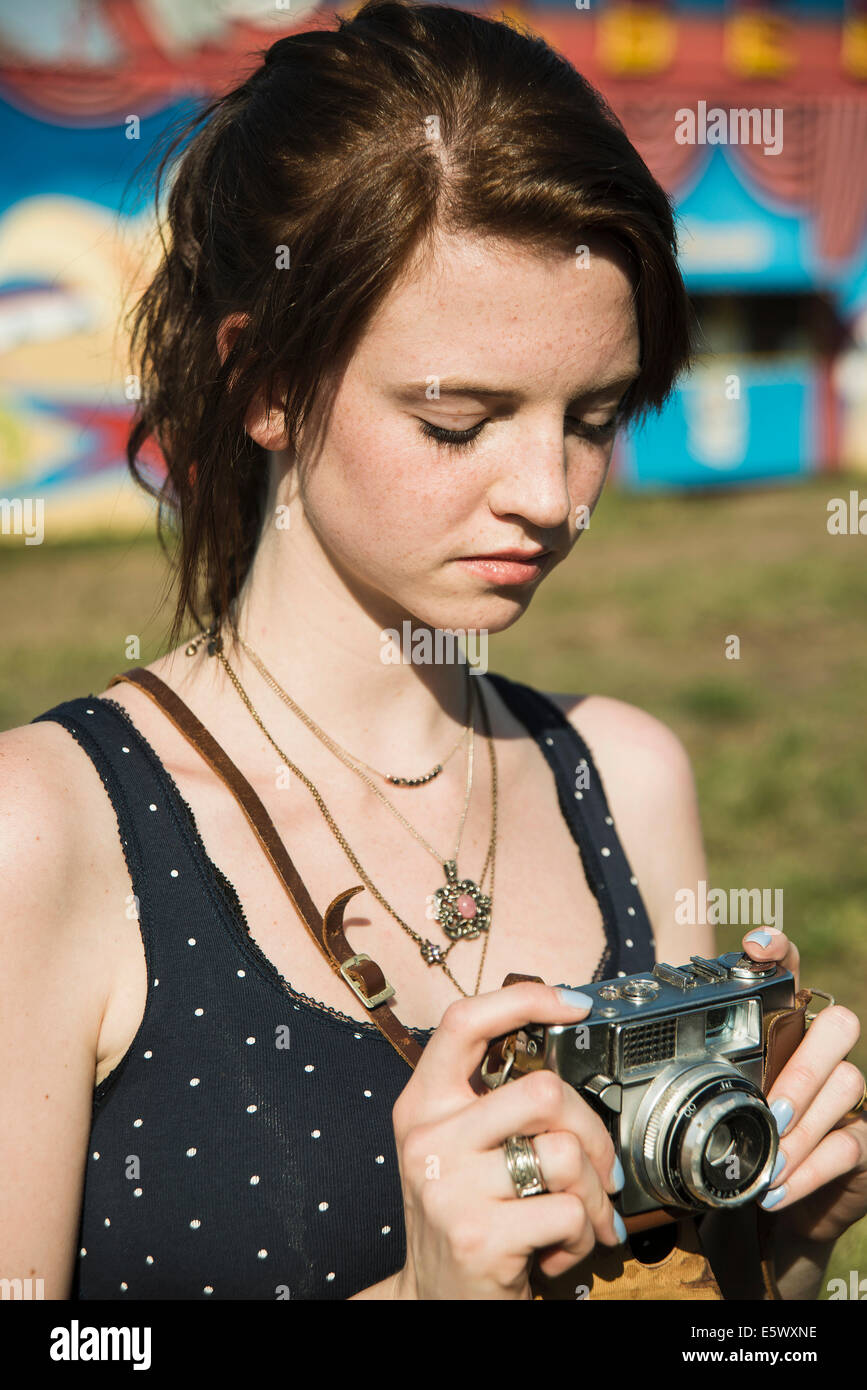 Young woman photographing on SLR camera at funfair - Stock Image