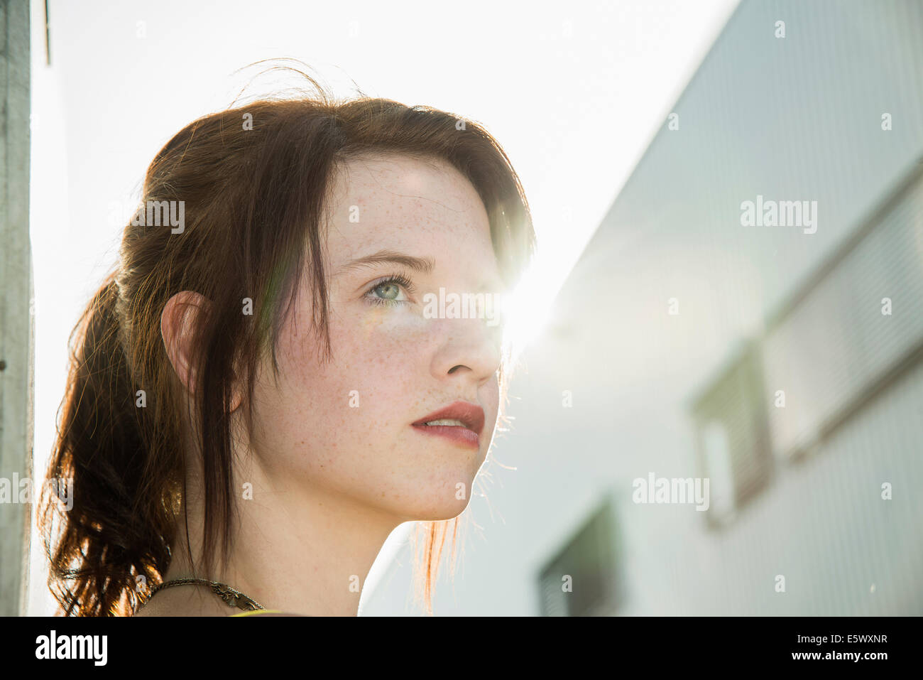 Portrait of sultry young woman on street - Stock Image