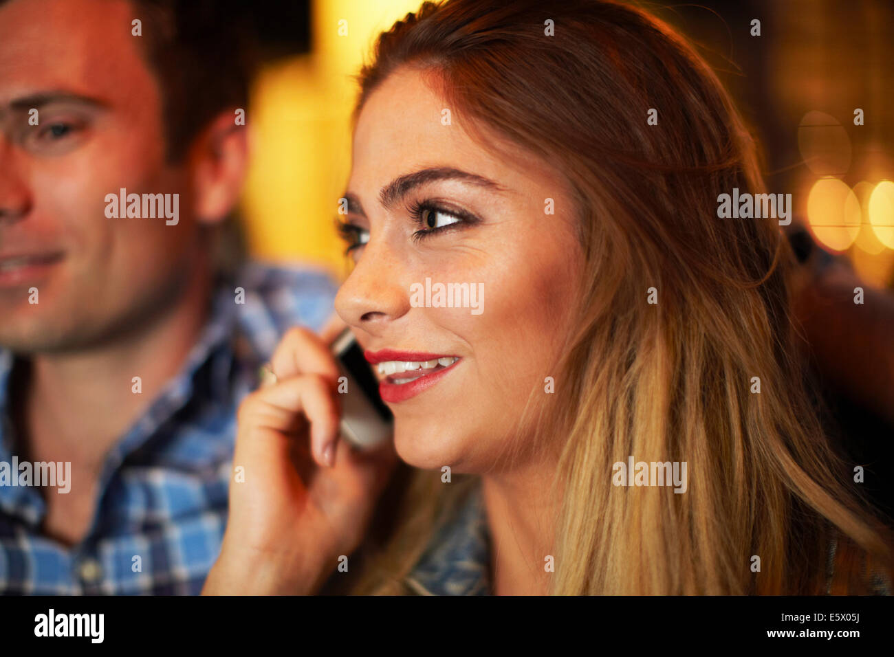 Young woman with boyfriend chatting on smartphone city taxi at night - Stock Image
