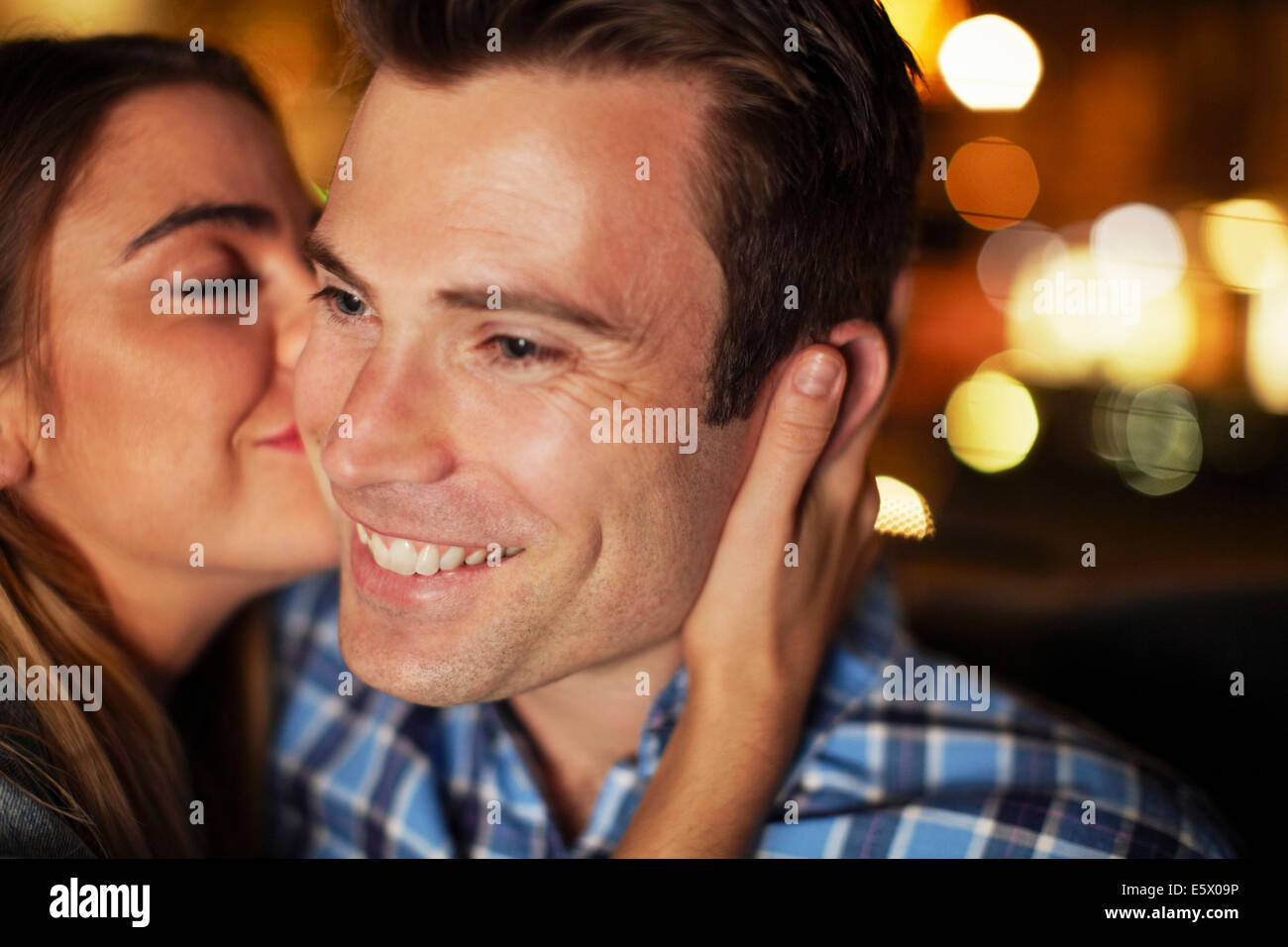 Couple sharing kiss on the cheek in city taxi at night - Stock Image